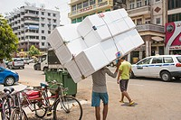 A young man carrying a big thing. Lanmadaw Township, Yangon, Myanmar.