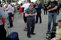 A man bends over to look at his smartphone while a crowd of people wait for the start of a ceremony involving hockey and the military.