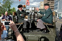Two military veterans hold the Memorial Cup trophy at the start of a city sponsored parade to honour the local junior hockey team that is the national...