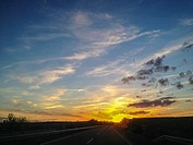 Driving on a highway at sunset. View from the inside of the car.