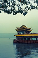 Tourist boat with typical flying eaves roof, moored on the West Lake, Hangzhou, Zhejiang province, China.