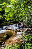 Young woman sitting by Davidson River in Pisgah National Forest - near Brevard, North Carolina, USA.