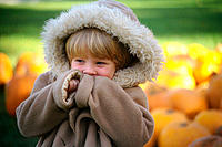 Young girl in oversized warm parka near pile of pumpkins