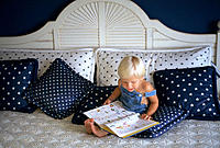 Young boy reading on bed