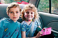 Two sisters as passengers in a car on a family outing