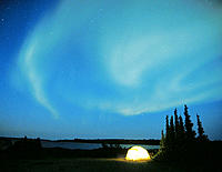 Northern Lights (aurora borealis) with lighted tent, Northwest Territories, Canada
