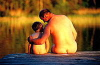 Nude father and son on dock