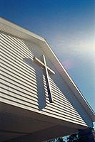 Cross on front of rural Christian church, sunlit, Monroe County, Indiana, USA