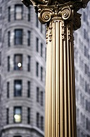 Corinthian column with Flatiron Building in background. New York City. USA