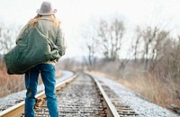 Woman with seabag on the rail road tracks