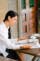 Young woman reading the newspaper at a sidewalk cafe