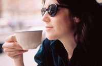 profile of a Woman in a coffe shop holding a cup wearing sun glasses looking out of the window