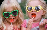 sisters with heart sunglasses and lollipops