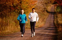 Couple jogging on country road