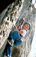 Young girl climbing rock face at rock climbing school
