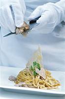 Chef putting white truffles to a dish of tagliolini. Hotel de Russie. Rome. Italy
