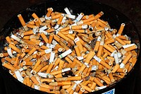 A diversity of filter cigarettes as cigarette butts in a huge ashtray in the outdoors in a special allocated smoking space for smokers