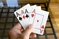 Hand Holding Four Aces
