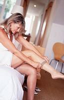 Mature woman pulling on stockings