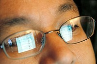 Laptop screen reflecting in an Asian-American man´s glasses as he surfs the Internet