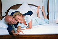 playful couple in bed ´fight´ for the remote