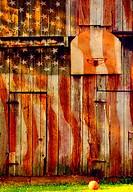 Warm light on basketball net on barn with US flag.