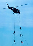 Army Rangers repelling out of a helicopter at military demonstration.