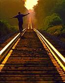 Man walking on railroad tracks.