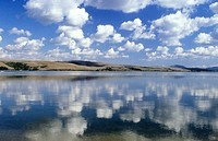 Cumulus clouds and dry hills reflected in Suisun Bay. Extreme east arm of San Francisco Bay. Solano co. (N) and Contra Costa co. (S), connected with S...