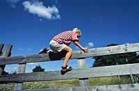 Boy climbing over a fence.