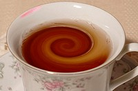Tea cup filled with whirling tea, with lipstick stain.