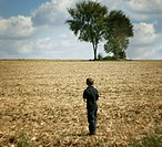 A boy looks to a copse of trees.