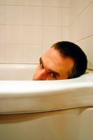 Man in bath tub taking a bath.