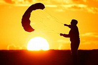 Boy playing with kite at sunset. Tarifa, Cádiz province. Andalusia, Spain