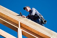 Carpenter walking along a roof rafter with a speed square at a construction site.