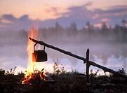 Coffee boiling over a campfire, at sunrise. Byske. Vasterbotten. Sweden.