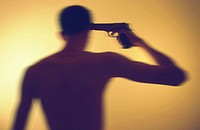 Silhouette of man with gun to his head