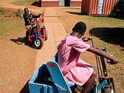 A young boy and girl use special carts to exercise their upper bodies during a physiotherapy session at the Kamapala School for the Physically Handica...