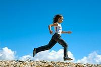 Girl running along seaside kicking