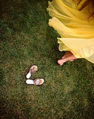 A woman spinning in a vintage yellow dress with her mother´s vintage shoes left behind.