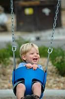 Toddler laughing on swing