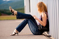 Young blonde woman is reading a road map while sitting by the wall with one leg lifted hight into air