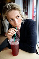 Caucassian businesswoman at cafe looking off sipping cool drink