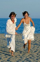 Newly young married couple running on the beach.