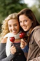 Teenage girls eating toffee apples