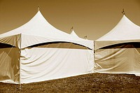 Circus tents with flags flying on top of tents, sepia toned, on grass