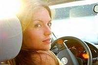 girl 18 yrs old driving car with evening sun peeking through.