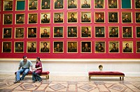 Couple seated in front of portrait gallery of the portrait gallery of the 1812 war heroes in the Hermitage Museum (Winter Palace). St Petersburg. Russ...