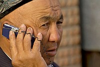 Uigur man talk to a mobile phone. Kashgar. Xinjiang province. China. Asia.