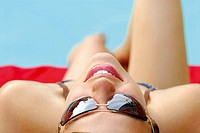 20 yr old woman laying by pool with sunglasses on